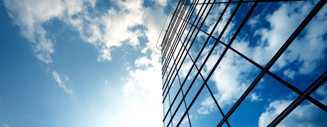 low angle of a skyscraper with reflective mirror-like windows and a blue sky with scattered clouds in the background